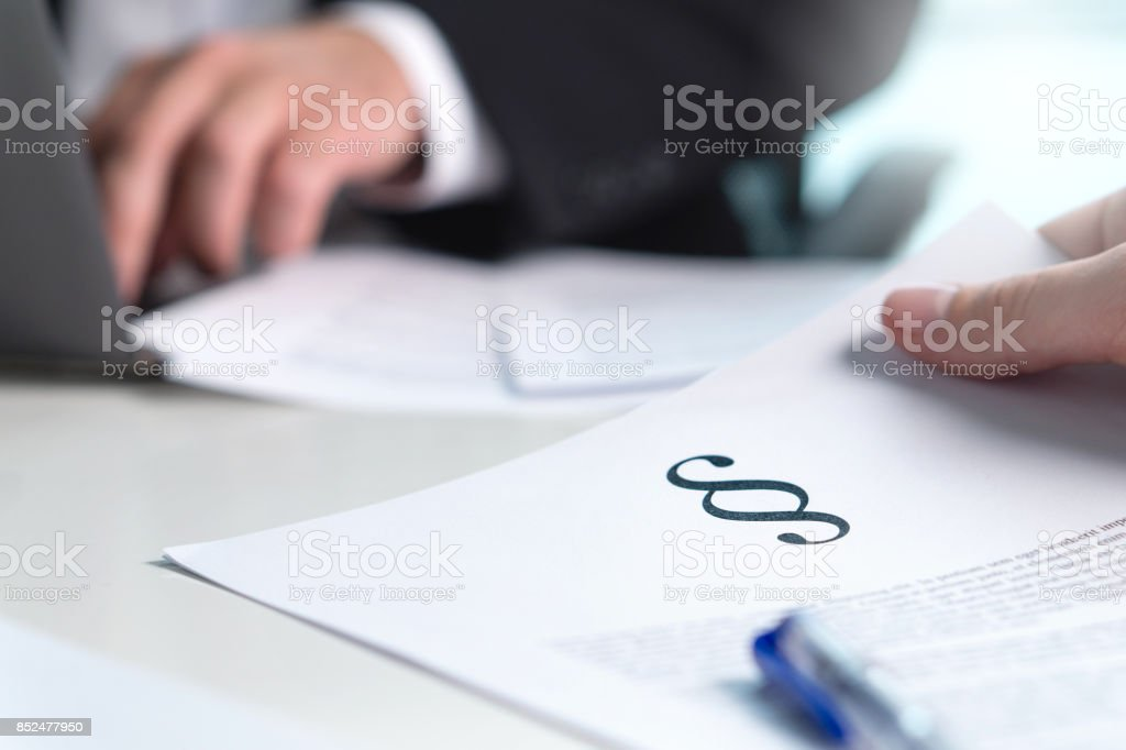 People in law firm having meeting. Lawyer giving legal advice to a client in office. Man holding a paper with a section sign. stock photo