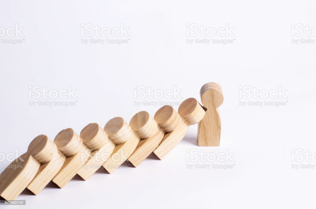 People in line fall like dominoes. Man stops the fall of people as dominoes. The concept of durability and strength, business ideas. Willpower, strong nerves, strong character. Stubbornness. stock photo