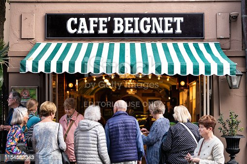 New Orleans, USA - April 23, 2018: People in line queue during day for famous restaurant cafe beignet powdered sugar donuts