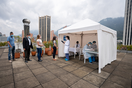 Group of Latin American people in line waiting to get their COVID-19 vaccine at a vaccination stand - immunization program concepts