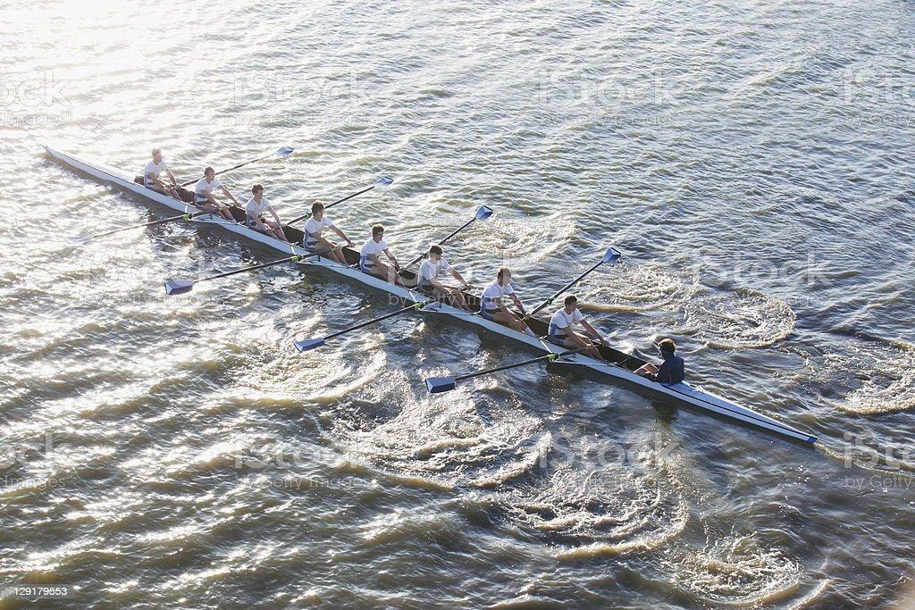 People in long canoe oaring stock photo