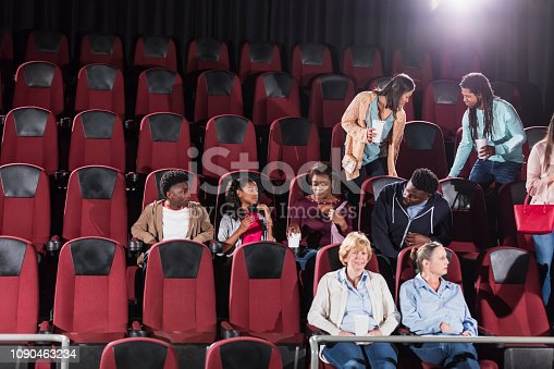 A multi-ethnic group of people getting ready to watch a movie in a movie theater, finding their seats. An African-American family with two children are sitting in a middle row.