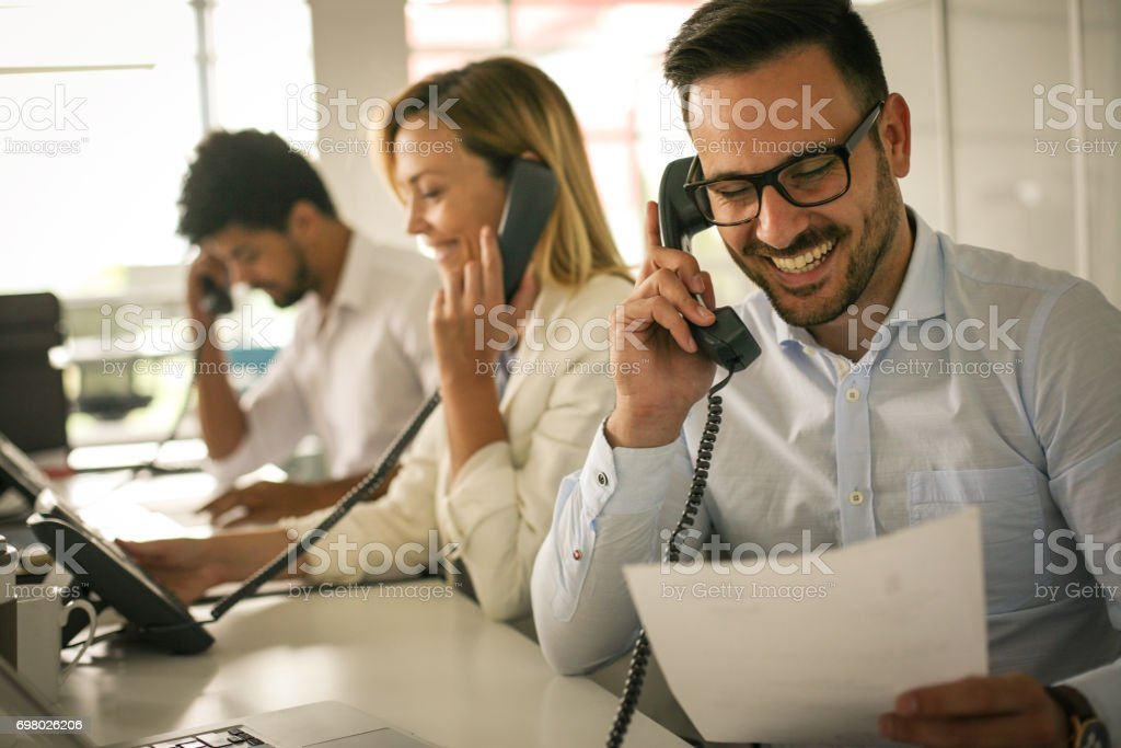 People in operations center  talking on Landline phone. Operators in the office. stock photo