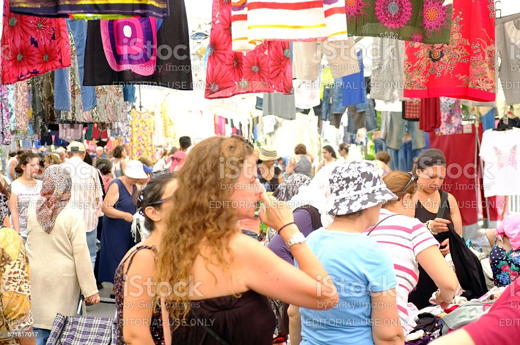 People shop outdoor clothing market in Akcay, Turkey.