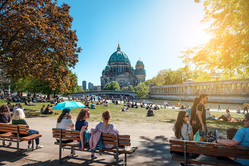 People in public park on a sunny day near Museum Island and Berlin Cathedral