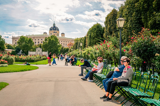 Vienna, Austria - September 10, 2019: Young and old people in public park Volksgarten. Natural History Museum and Museum of Fine Arts at background. Colorful rose bushes, vintage lights and walkway.