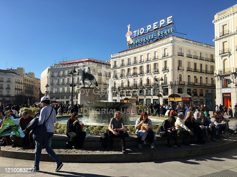 Madrid, Spain - February 23, 2020: People sitting around fountain in the famous Puerta del Sol in the city downtown. This is one of the best known and busiest places in the city. This is the centre (Km 0) of the radial network of Spanish roads