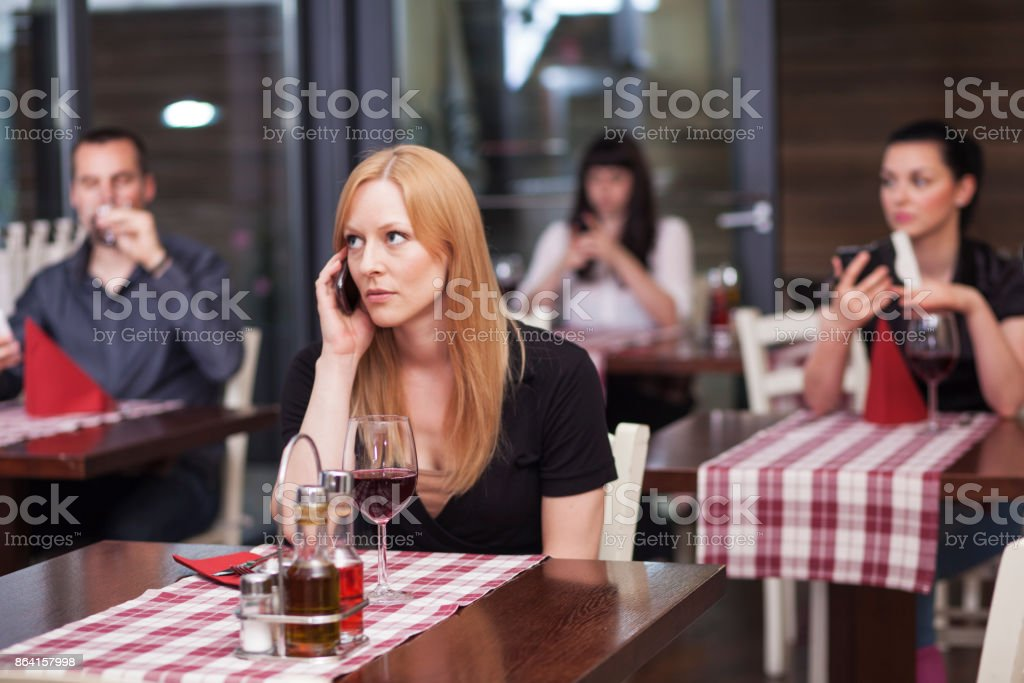 People in restaurant all using phones royalty-free stock photo