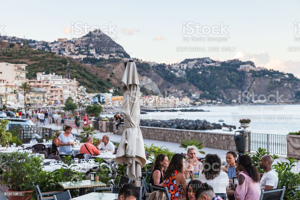 people in sidewalk restaurant in Giardini Naxos stock photo