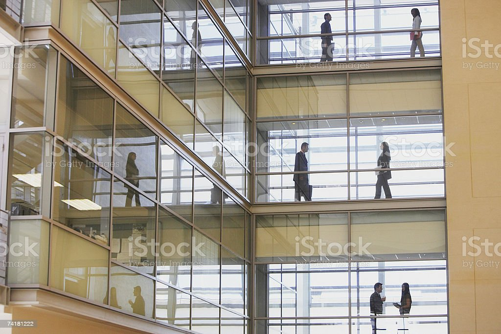 People in silhouette on multiple levels of corridor through glass royalty-free stock photo