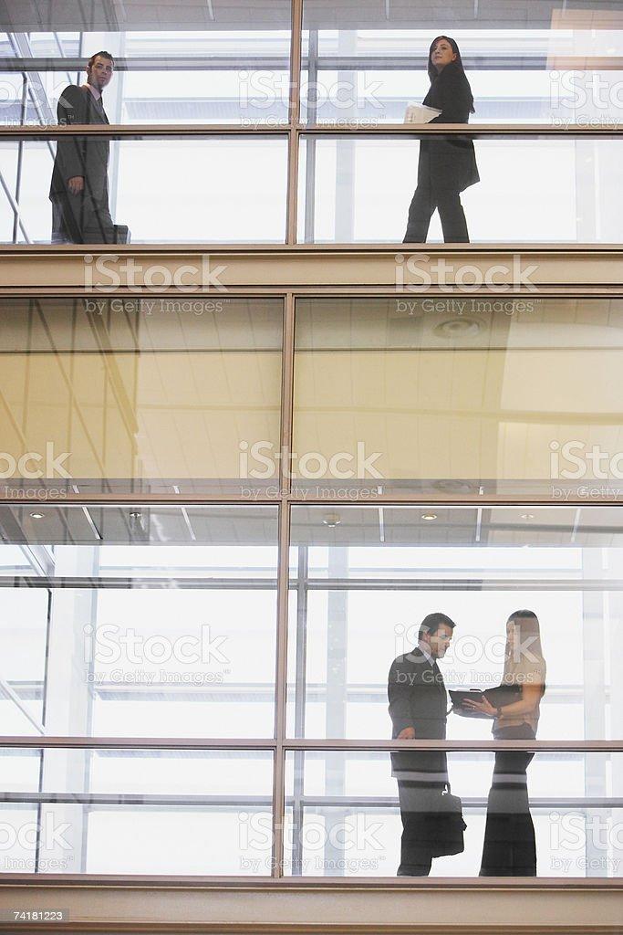 Personas en silueta en múltiples niveles, del corredor a glas foto de stock libre de derechos