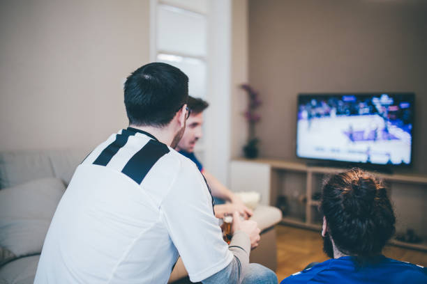 People in sport jerseys watching TV at home Three men talking and watching sports channel on TV man bun stock pictures, royalty-free photos & images