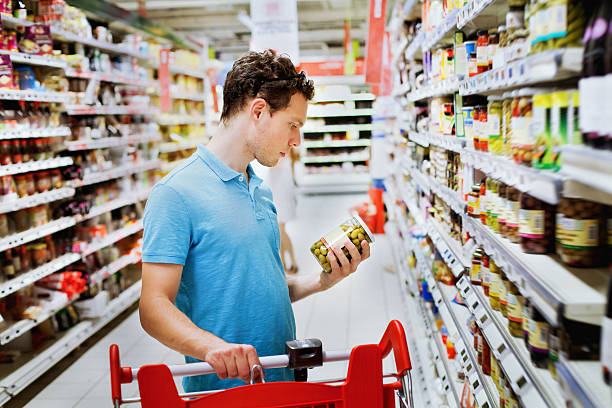 people in supermarket choosing food shopping concept, man reading label on the jar snack aisle stock pictures, royalty-free photos & images