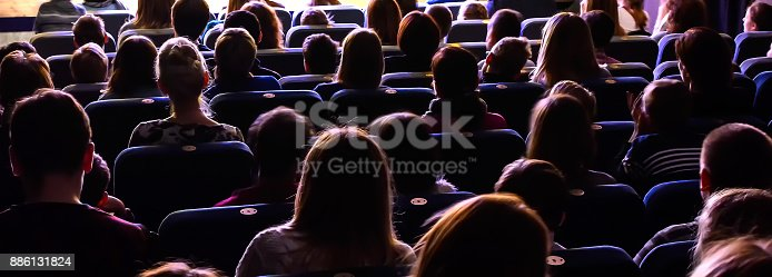 People in the auditorium watching the performance. The audience in the theater.