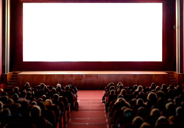 People in the cinema auditorium with empty white screen. stock photo