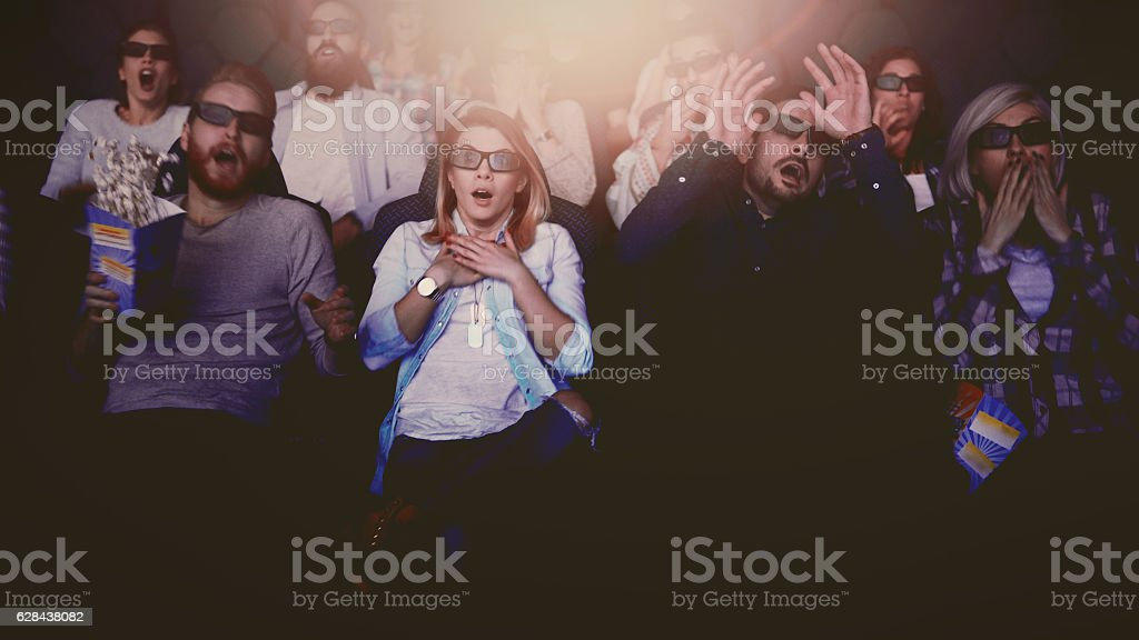 people in the cinema watching a 3d horror movie stock photo