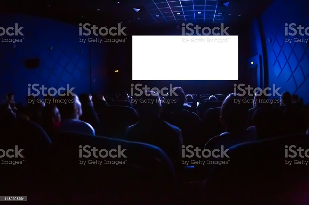 People in the cinema watching a movie. Blank empty white screen People in the cinema watching a movie. Blank empty white screen. Adult Stock Photo