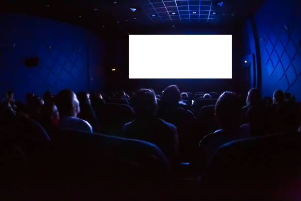 people in the cinema watching a movie. blank empty white screen - film industry stock pictures, royalty-free photos & images
