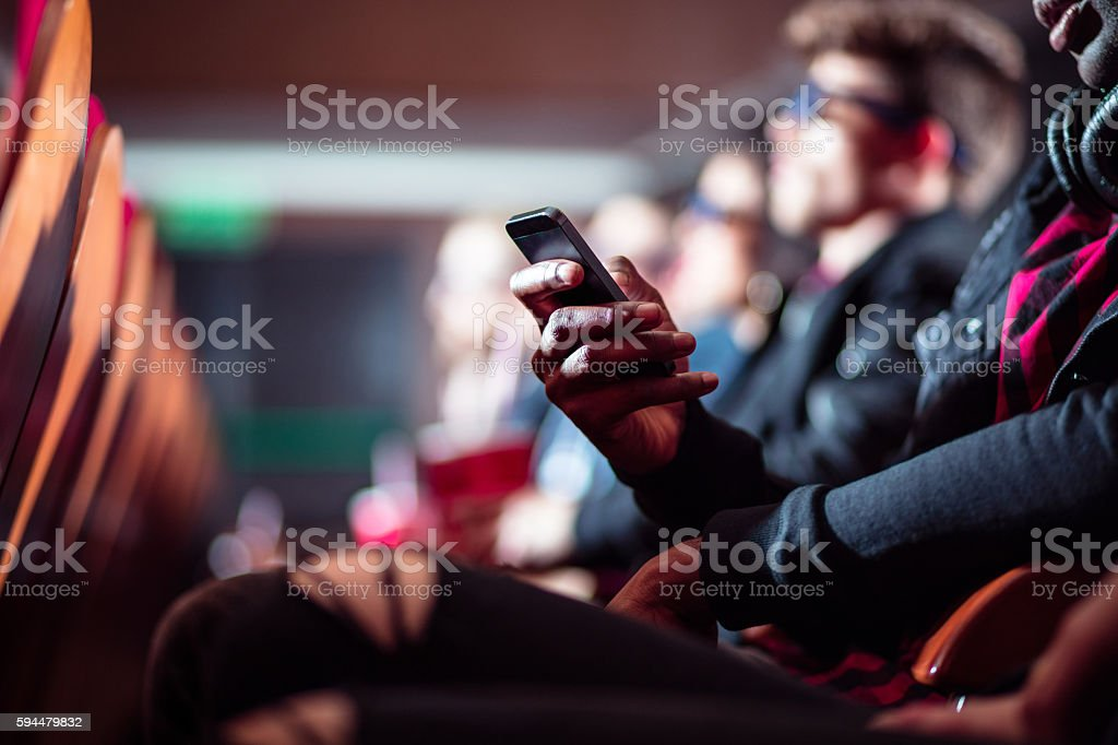 People in the movie theater, close up of mobile stock photo