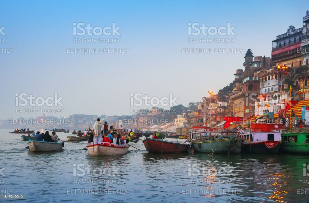 People in tourist boats and on holy ghats among hindu temples at river Ganga wait for sunrise in the early morning in Varanas stock photo