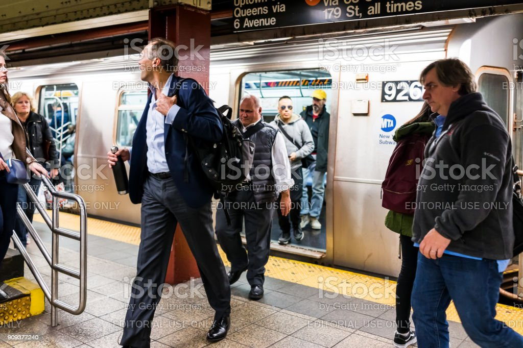 People in underground platform transit in NYC Subway Station after work on commute with train, business people walking out arriving at rush hour stock photo