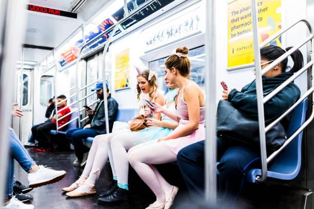 menschen in unterirdischen transit in nyc u-bahn-station mit zug auto, leute sitzen in ballerina halloween kostüme mädchen frauen - festzugskleidung stock-fotos und bilder