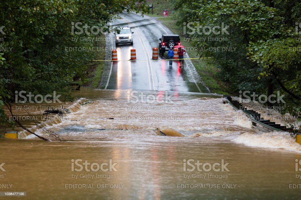 People in Union County, NC are blocked from crossing a road flooded by Hurricane Florence stock photo