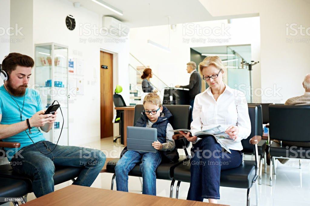 Indoor shot of people sitting in the reception area waiting for their...