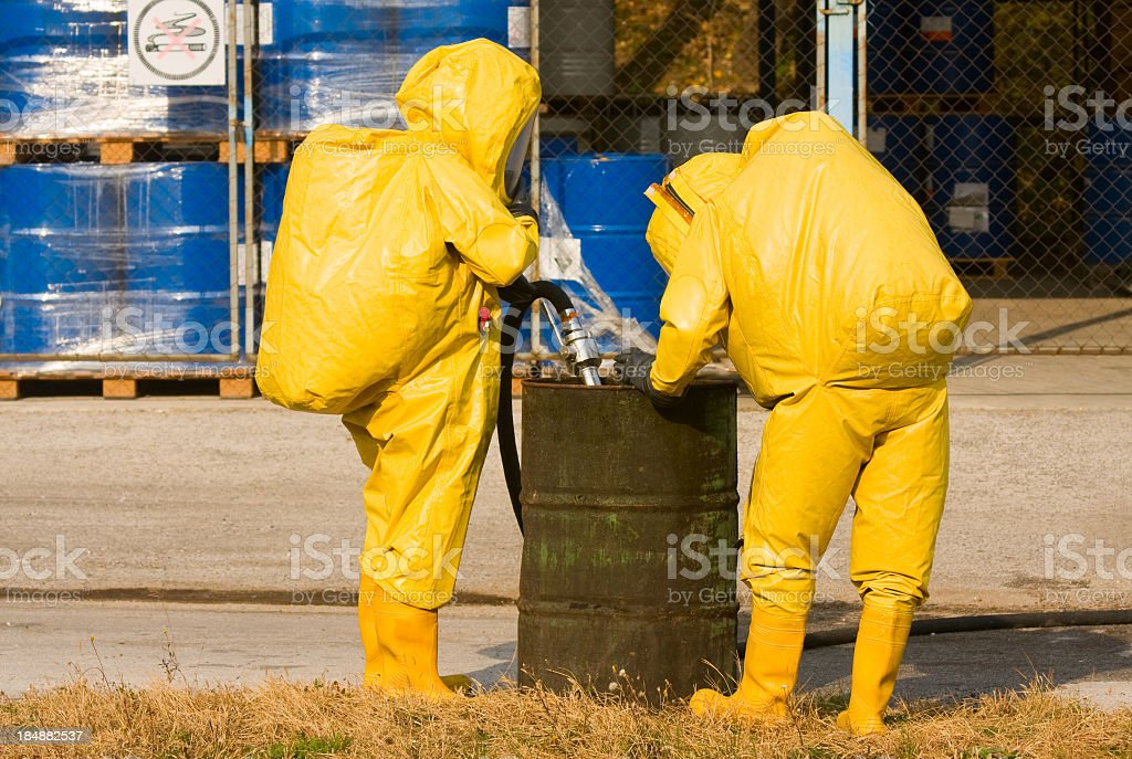 People in Yellow Suits Collecting Hazardous Material stock photo