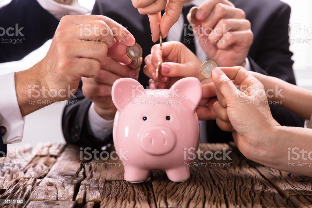 Personen einfügen Münzen ins Sparschwein – Foto