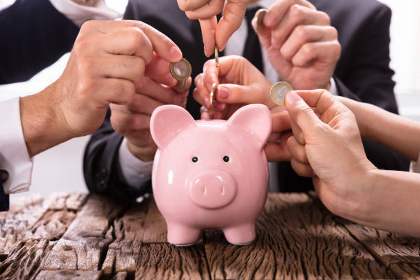 People Inserting Coins Into Piggybank stock photo