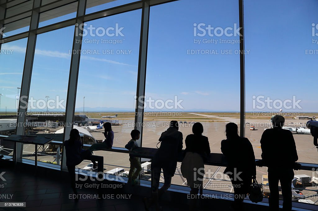 People inside YVR airport watching air canada airplane stock photo