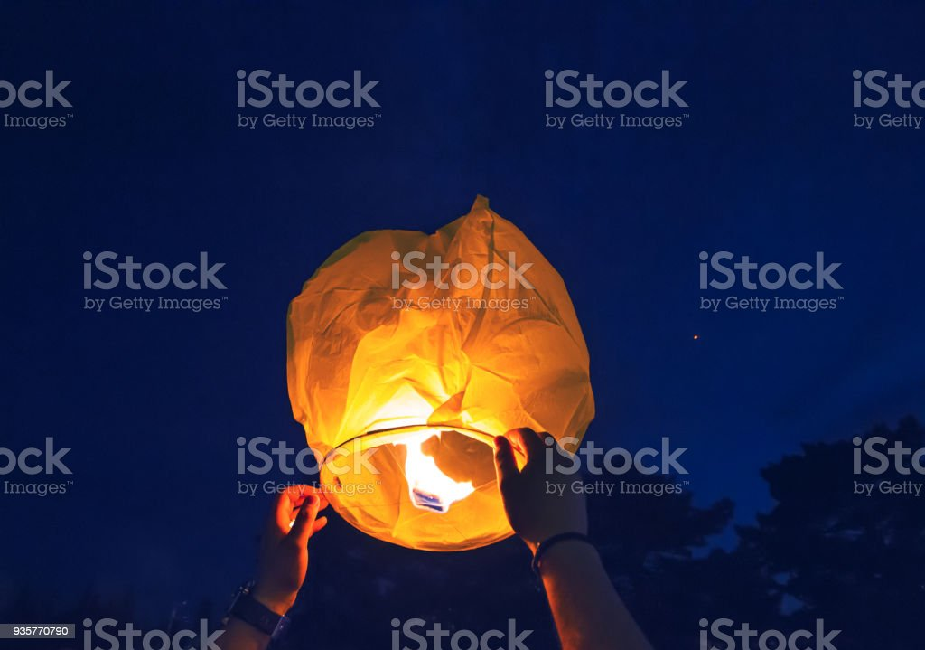 People is launching sky lantern to the sky stock photo