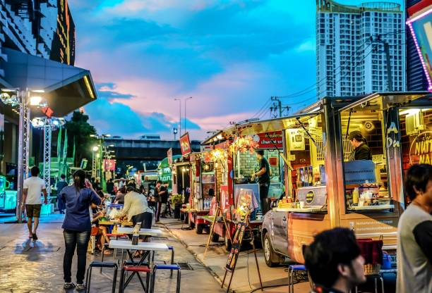 People joined foodtruck event in the night, happy to buying food, meeting friends, waiting and eating dinner from foodtruck shop. BANGKOK, THAILAND - 10 November, 2017: People joined foodtruck event in the night, happy to buying food, meeting friends, waiting and eating dinner from foodtruck shop. This event near to RCA. (Royal City Avenue) lahore pakistan stock pictures, royalty-free photos & images