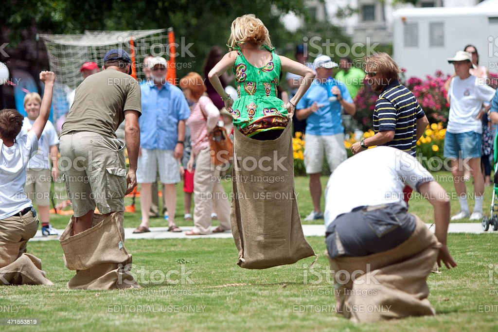 People Jump In Sack Race At Spring Festival stock photo