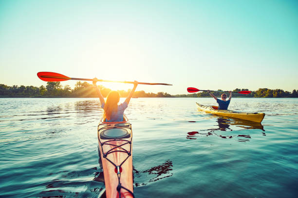 People kayak during sunset in the background. Have fun in your free time. stock photo