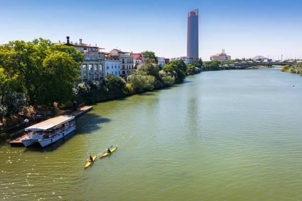 People kayaking down Guadalquivir river in Seville, Spain stock photo