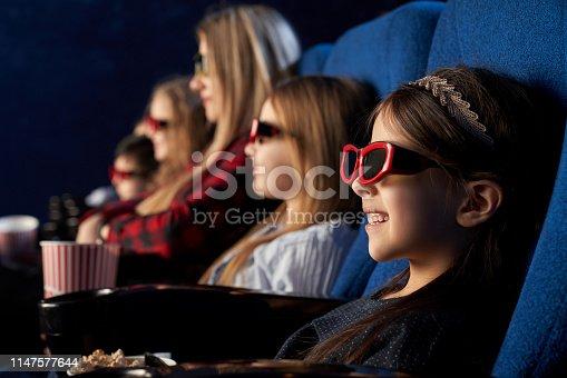 istock People, kids watchng movie in 3d glasses in cinema. 1147577644