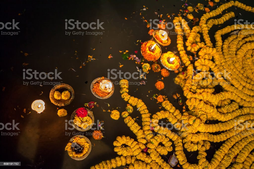 People kindle lamps with flowers in evening time Varanasi stock photo
