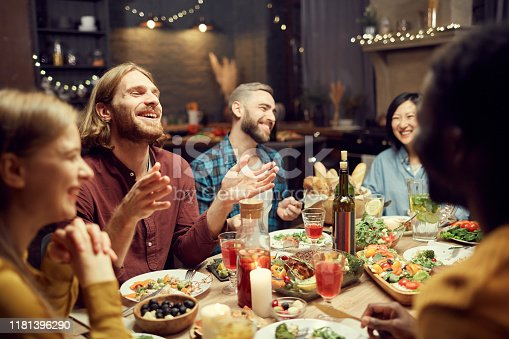 Group of emotional young people enjoying dinner party with friends and smiling happily sitting at table in dimly lit room, copy space