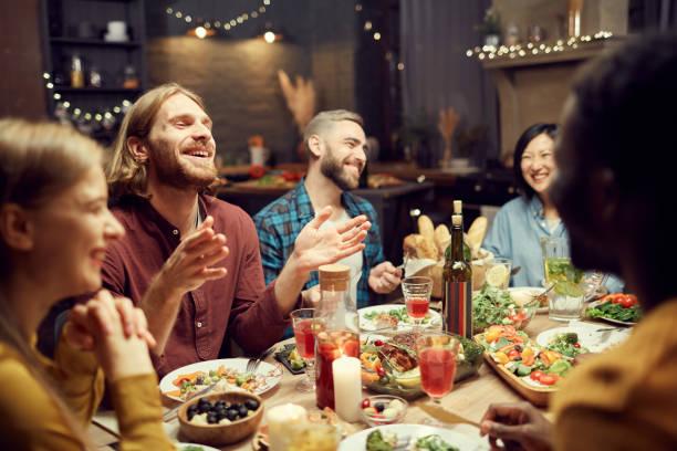 gente riendo en la mesa de la cena - restaurante fotografías e imágenes de stock