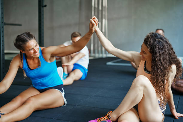 People laughing together on a gym floor after working out Two smiling young female friends in sportswear high fiving each other while sitting on the floor of a gym encouragement stock pictures, royalty-free photos & images