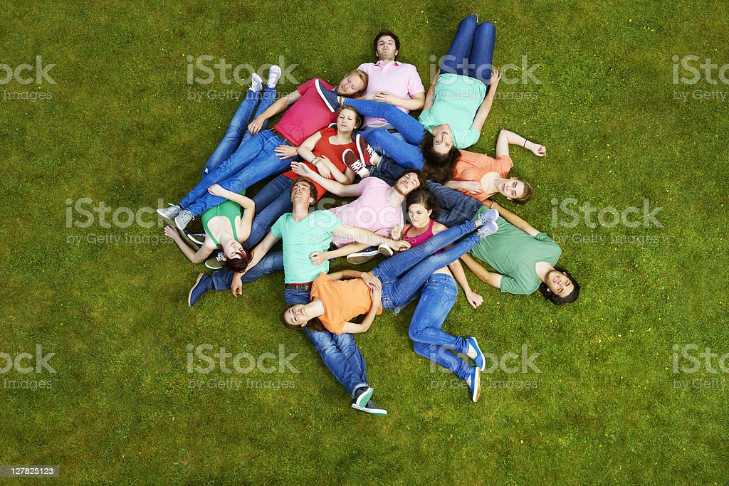 People laying in dogpile outdoors stock photo
