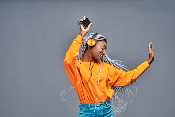 People, life, energy and music concept. Glad woman rejoices something, enjoys nice sound in new headphones, uses smartphone, listens song from playlist, spends time for dancing and entertaining stock photo