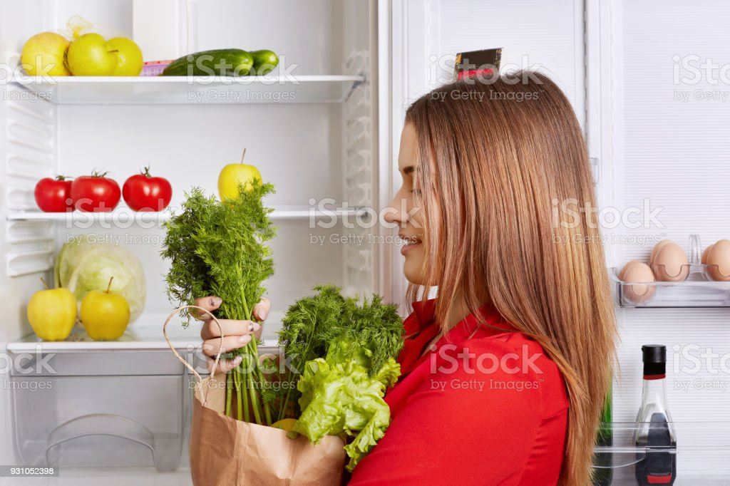 People, lifestyle and healthy eating concept. Sideways shot of adorable woman holds paper box with dill and lettuce, has fridge full of fruits and vegetables, going to make vegeterian fresh salad stock photo