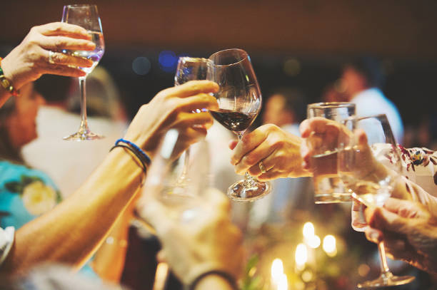 People lifting Glasses of Wine celebratory toast Glasses of wine lifted together in a celebration toast Stellenbosch Cape Town South Africa western cape province stock pictures, royalty-free photos & images