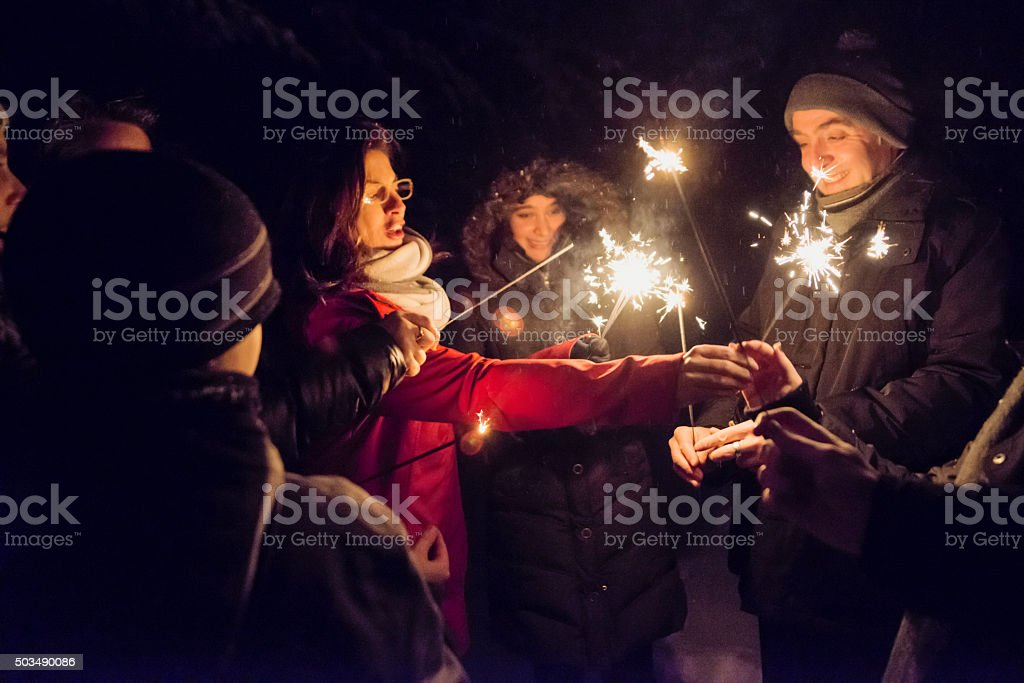 People lighting sparkling Bengal fire outdoors at night in winter. stock photo