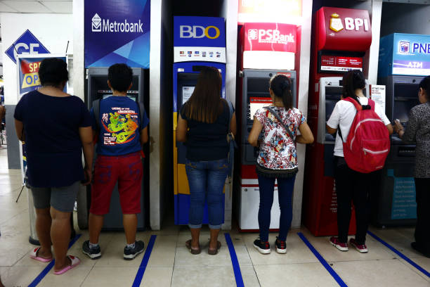 people line up and get cash from bank atm machines at a commercial center. - depositor stock pictures, royalty-free photos & images