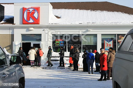 people lined up outside a gas station to pay for gas and purchase emergency supplies after a record breaking snow storm, St. John's, Newfoundland, Canada.