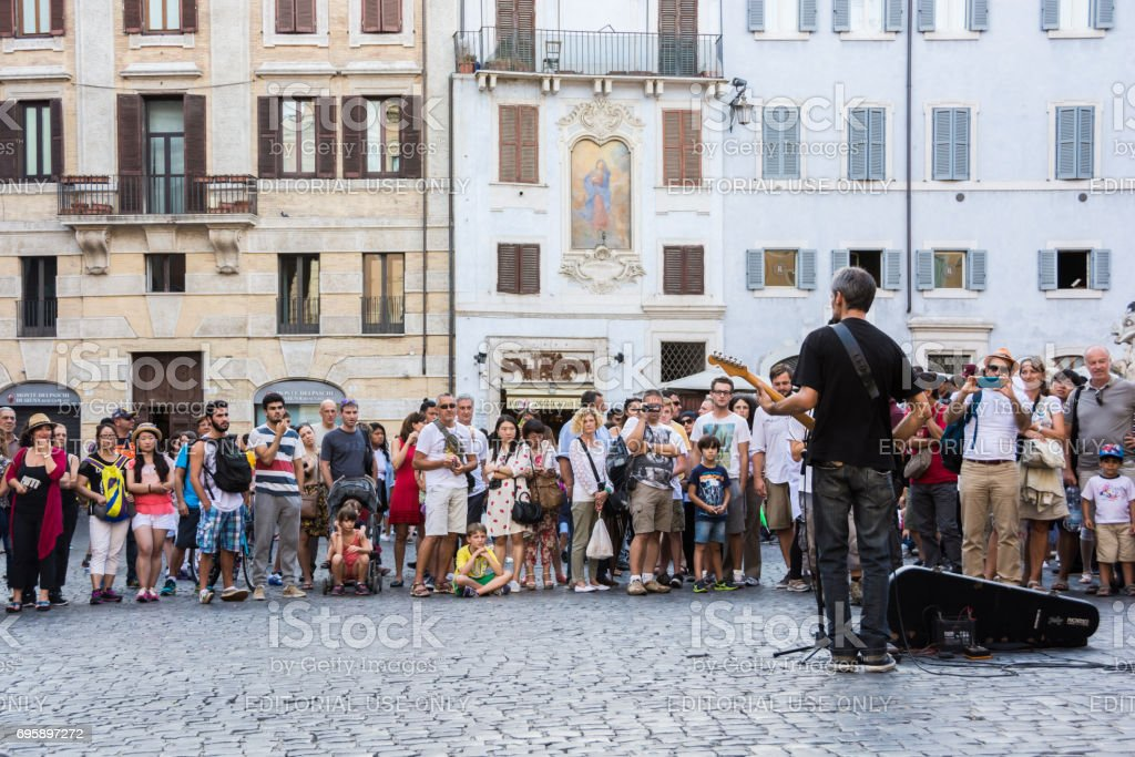 ROME, ITALY - AUGUST 16 2015: People listening to a man playing the guitar, Rome stock photo